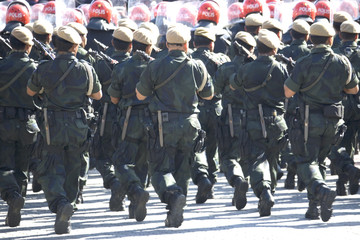 Image of armed uniformed police marching.