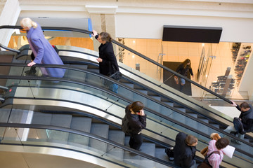 Peoples on escalators in a mall. Motion blur