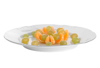 Peeled tangerines and grapes on plate isolated on white
