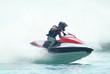 Man riding a powercraft through the sea spray - 5560385