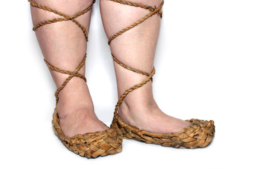 peasant woman legs in russian bast shoes on white background