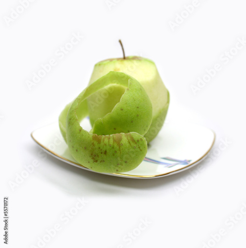 Green apple and its peel on plate on white background