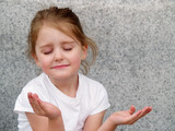 little girl with upturned hands as in prayer or meditation