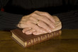 old hands with weddingring resting at closed antique bible
