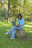 Young woman buying online something outdoor in a forest. poster