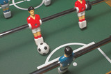 A miniature tabletop foosball arcade type game. poster