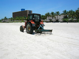 tractor cleans up sand in Varadero, Cuba poster