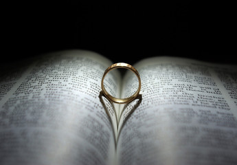 Wedding Ring and heart shaped shadow over a Bible
