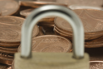 Euro coins viewed through padlock bail.