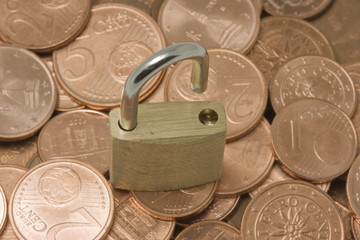 Opened padlock on top of pile of coins