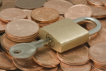 Padlock with key on top of a pile of coins