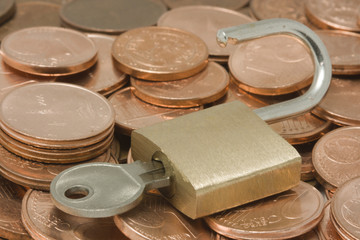 Opened padlock with key on top of pile of coins