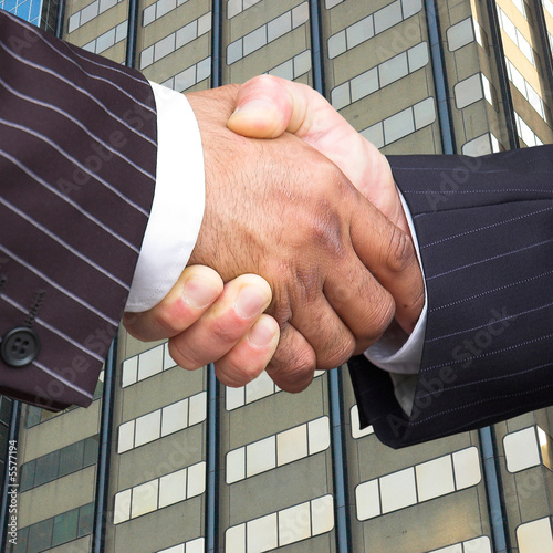 Businessmen in pinstripe suits shake hands.