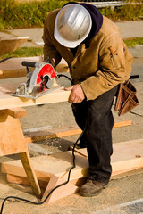 Construction worker cutting piece of lumber with saw