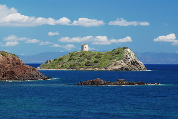 Ancient fort on a small island in the sea on Sardinia coast