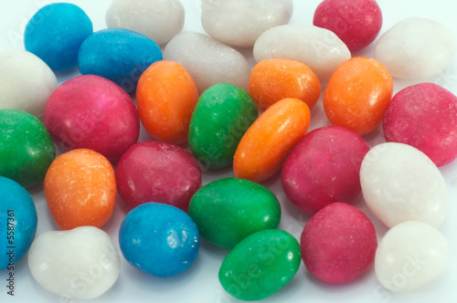 scatter multicolored icing glaze sweeties on white