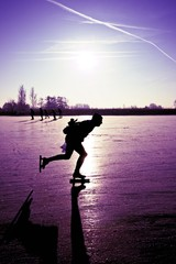 Ice skating with a beautiful purple sunset in the Netherlands