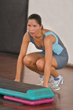 Image of a young woman during aerobics training in a gym. poster