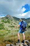Hiker at Prevalski lake in national park Pirin, Bulgaria poster