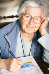 Senior woman solving crossword puzzle, portrait