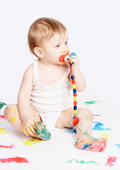 The baby with a dummy sits on a paper