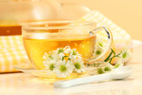 Glass tea cup with herbal tea and flowers poster