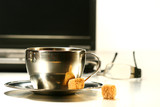 Stainless steel coffee cup with laptop in background poster
