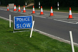 blue police slow sign with warning cones in the road poster