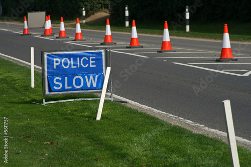 blue police slow sign with warning cones in the road