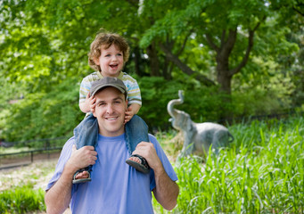 Toddler rides on Dad's shoulders in the zoo.