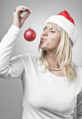 Blond Swedish girl in santa hat kissing christmas ball