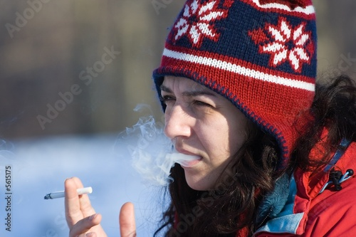 Woman smoking in a winter day