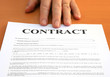 Male hand presents a contract document
