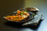 mussel with garlic sauce and parsley on black table poster