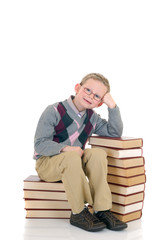 Young boy leaning on stack of books,