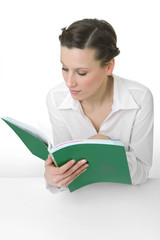 Happy young woman reading a big book