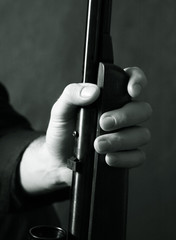 The weapon in a man's hand on a dark background