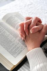 Female hands clasped in prayer ove a Bible