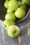 Green Granny Smith apples, spilling from a rusted bucket  poster