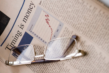 Business newspaper and glasses, alternative angle