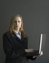 RothaarigeGeschäftsfrau hält einen Laptop