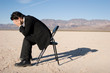 Businessman sitting alone in the empty desert