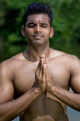A well-built young man practising yoga outdoors