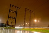 Electric pillars on a rainy night next to a highway