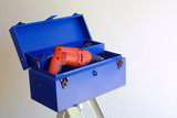 Blue diy home improvement toolbox with orange drill poster