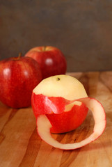 Partially pealed apple with two apples in the background