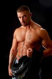 A muscular bodybuilder undressing poster