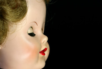 A close up of an antique doll with her eyes closed