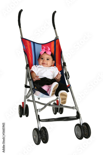 Happy baby girl in stroller over white background. Full body.