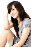 A cute young Asian teenager in grey dress on white background poster